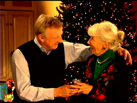 senior man giving christmas gift to surprised wife - see other clips from this shoot 1407 stock videos and b-roll footage
