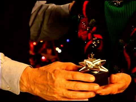 senior man giving christmas gift to wife - see other clips from this shoot 1407 stock videos and b-roll footage