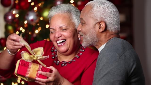 ms pan senior man giving christmas present to wife / richmond, virginia, usa - 贈り物点の映像素材/bロール