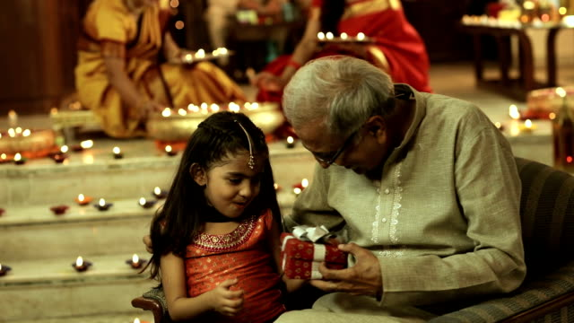 senior man giving gift to his granddaughter, delhi, india - grandfather stock videos & royalty-free footage