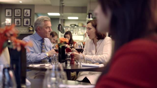 stockvideo's en b-roll-footage met ms pan senior man giving gift to woman in restaurant - geven