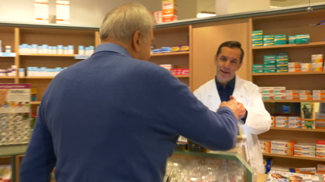 senior man giving prescription to pharmacist - prescription medicine stock videos and b-roll footage