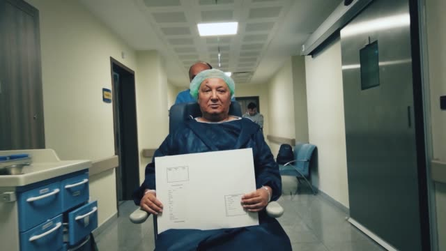 senior man going to surgery on wheelchair at hospital corridor - first aid stock videos & royalty-free footage