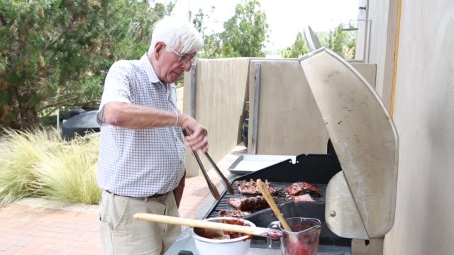 senior man grilling ribs