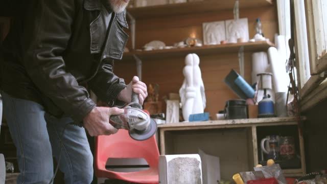 vidéos et rushes de senior homme son oeuvre d'art dans le garage de meulage - sculpture production artistique