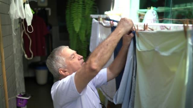 vídeos y material grabado en eventos de stock de hombre mayor colgando ropa en el tendedero - cuerda de tender la ropa