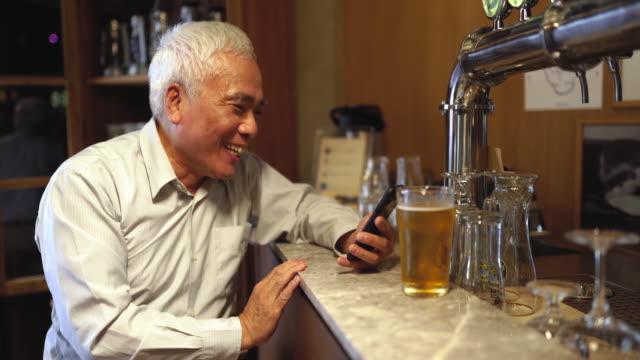 vídeos de stock, filmes e b-roll de homem sênior que tem a cerveja na barra - idoso na internet