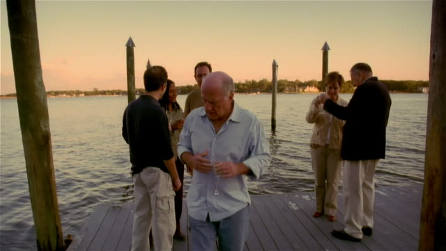 vídeos de stock, filmes e b-roll de senior man having heart attack during party on lakeside dock - heart attack