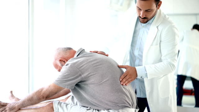 senior man having his back examined by a doctor. 4k - physical therapy stock videos & royalty-free footage