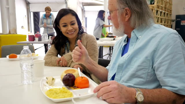 Senior man having meal in soup kitchen with young volunteer