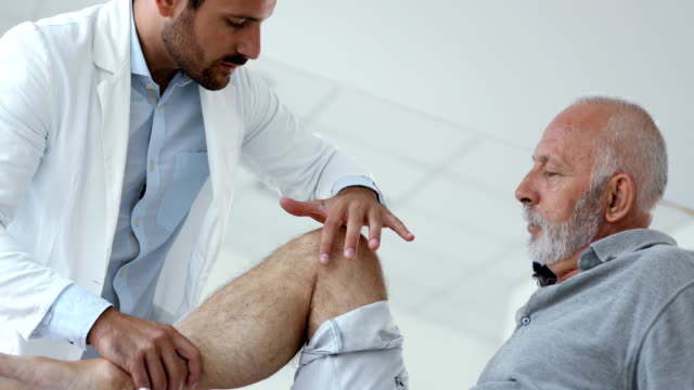 senior man having medical exam. - inginocchiarsi video stock e b–roll