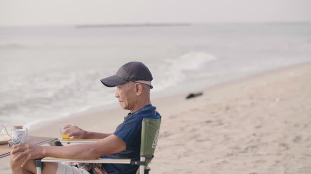 senior man having orange juice while relaxing on the beach. - chair stock videos & royalty-free footage
