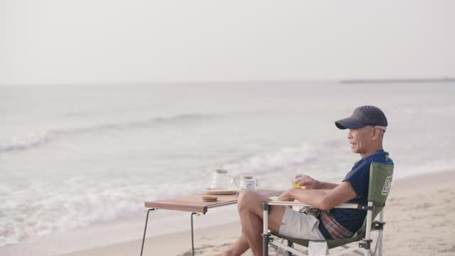 vídeos y material grabado en eventos de stock de hombre mayor tomando jugo de naranja mientras se relaja en la playa. - cámara en mano