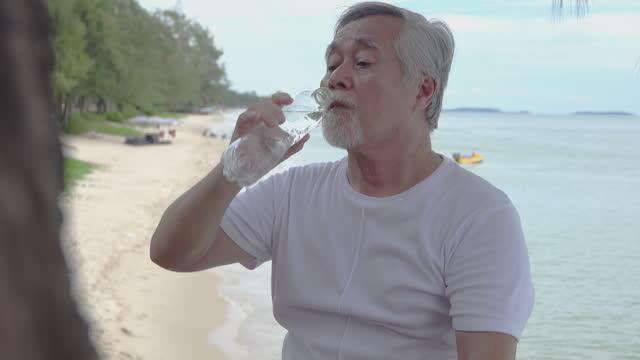 vídeos y material grabado en eventos de stock de un anciano cuidado de la salud en la playa. - posa del loto