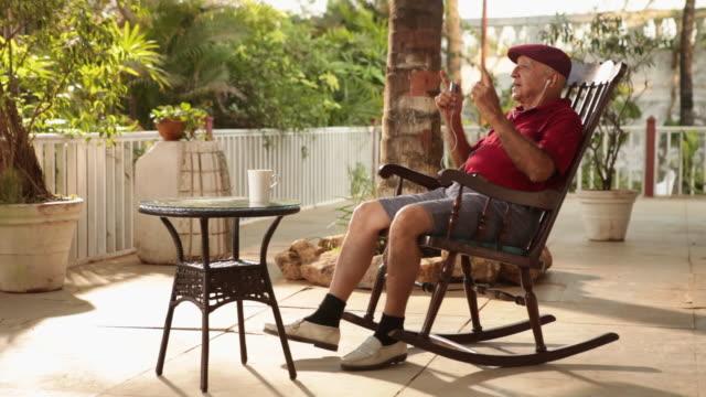 senior man hearing mp3 player  - rocking chair stock videos & royalty-free footage