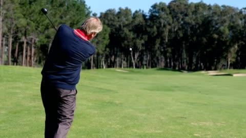 senior man hits a golf shot towards the putting green - golfer stock videos & royalty-free footage