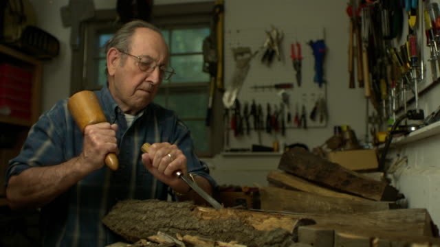 ms slo mo senior man hitting wood chisel with wood mallet in workshop / morristown, new jersey, usa - 薄毛点の映像素材/bロール