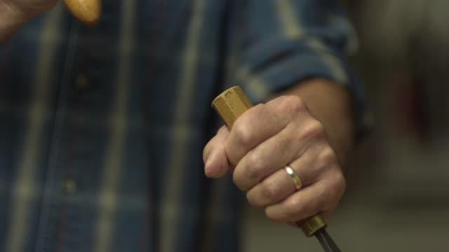 vídeos y material grabado en eventos de stock de cu senior man hitting wood chisel with wood mallet in workshop / morristown, new jersey, usa - herramienta de mano