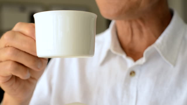 senior man holding a cup of tea - tea cup stock videos & royalty-free footage