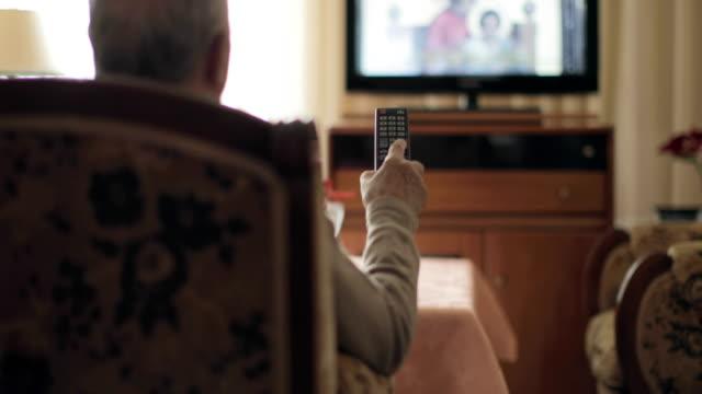 vídeos de stock, filmes e b-roll de senior man holding a tv remote control - homens idosos