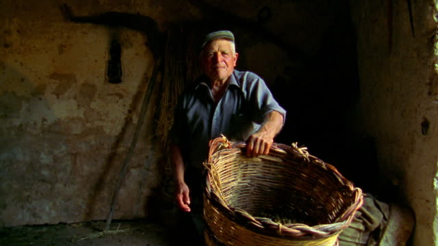ms senior man holding basket in barn / custonaci, sicily - sicily stock videos & royalty-free footage