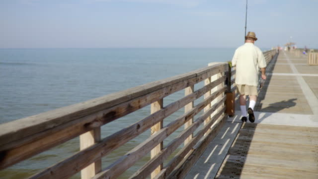 ws senior man holding fishing pole walking on pier / jacksonville beach, florida, usa    - one senior man only stock videos and b-roll footage