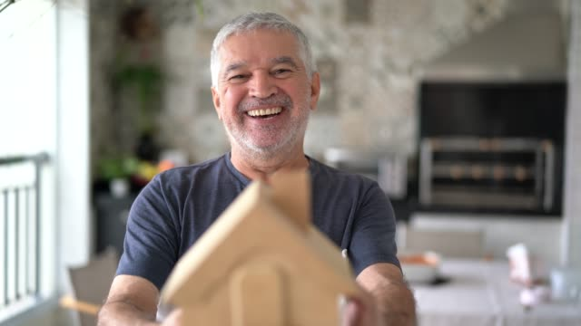 senior man holding house miniature or home model - model house stock videos and b-roll footage