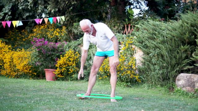 vidéos et rushes de hula homme senior hooping dans l'arrière-cour. - jeune d'esprit