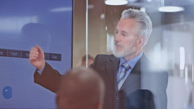 vídeos de stock e filmes b-roll de senior man in a business suit holding a presentation - parte de uma série
