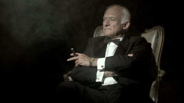 vídeos de stock e filmes b-roll de senior man in a dinner jacket, smoking a cigar - authority