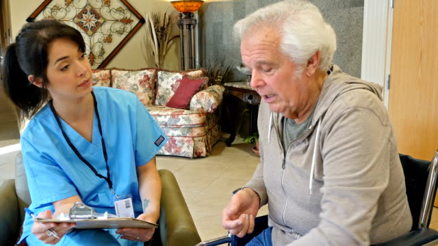 Senior man in assisted living facility meeting with staff nurse to discuss injury and healthcare