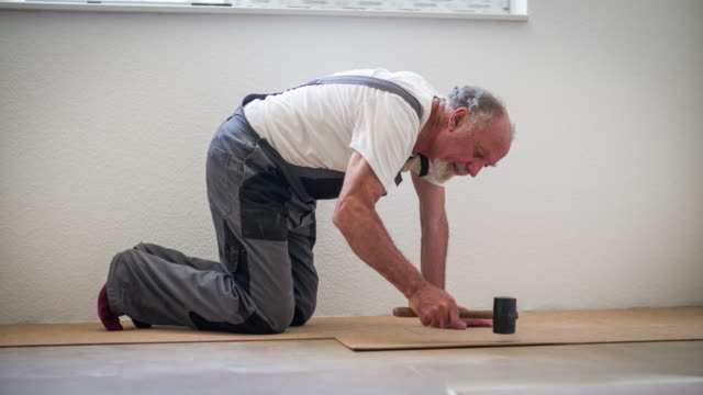 senior man in bib overall laying cork flooring in his house - cork material stock videos & royalty-free footage