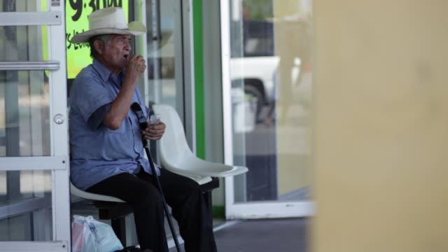 vídeos de stock, filmes e b-roll de senior man in cowboy hat sitting in front of store and waiting - só um homem idoso
