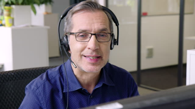 senior man in customer service position talking on the headset - desktop pc stock videos & royalty-free footage