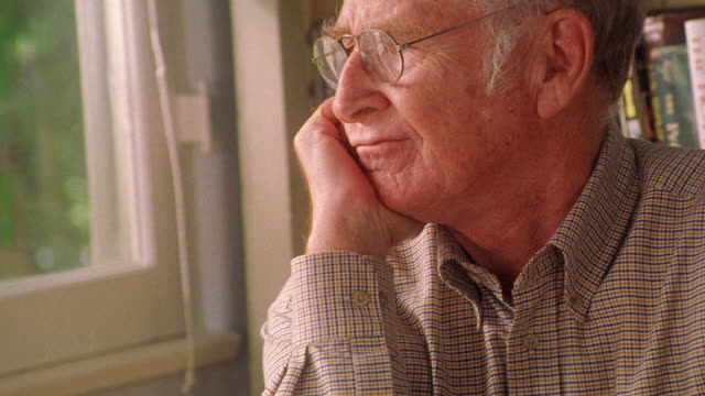 MS PROFILE senior man in eyeglasses resting chin on hand looking somber + sighing