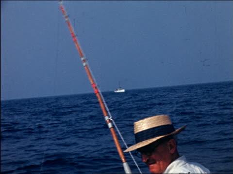 vidéos et rushes de 1941 home movie senior man in hat deep sea fishing off end of boat / waves to camera - chapeau de paille