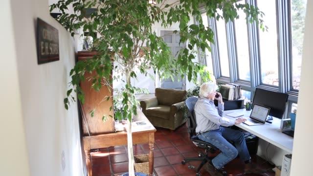 vidéos et rushes de senior man in home office - seniornaute