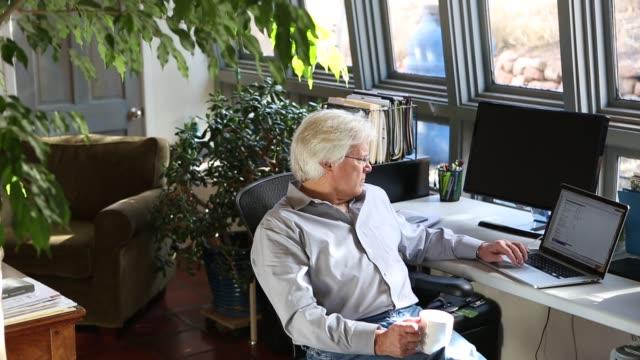 vídeos de stock e filmes b-roll de senior man in home office - idoso na internet