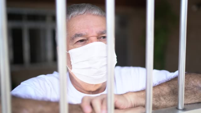 senior man in isolation at home for virus outbreak looking through window - prison window stock videos & royalty-free footage