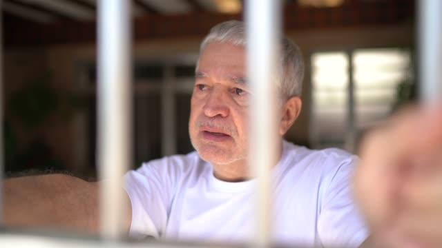 senior man in isolation at home looking through window - senior men stock videos & royalty-free footage
