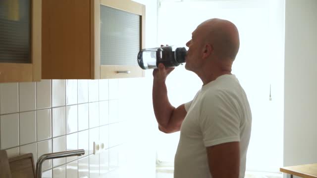 vídeos de stock, filmes e b-roll de homem sênior na cozinha beber da garrafa de água - sedento