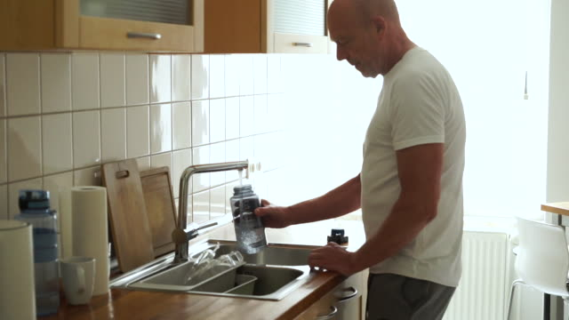senior man in kitchen filling sport water bottle - filling stock videos & royalty-free footage