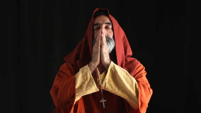 Senior Man In Medieval Priest Costume Praying