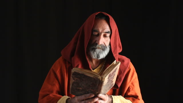 alter mann im mittelalterlichen priester kostüm lesen bibel - historische kleidung traditionelle kleidung stock-videos und b-roll-filmmaterial