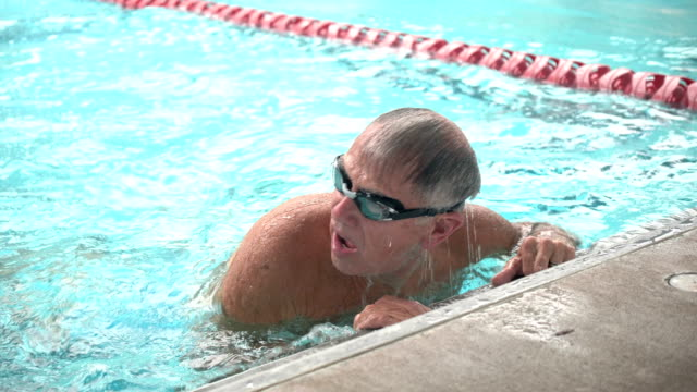 senior man in pool swimming laps - swimming stock videos & royalty-free footage