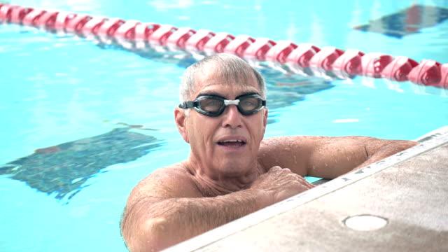 senior man in pool taking break from swimming laps - length stock videos & royalty-free footage