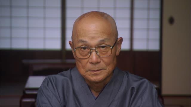 cu portrait senior man in robe bowing/ tokyo, japan - bowing stock videos & royalty-free footage