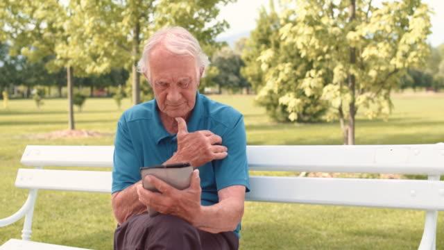 vídeos de stock e filmes b-roll de homem idoso no parque trabalhar num tablet - idoso na internet