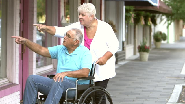 senior man in wheechair with wife, window shopping - disability stock videos & royalty-free footage