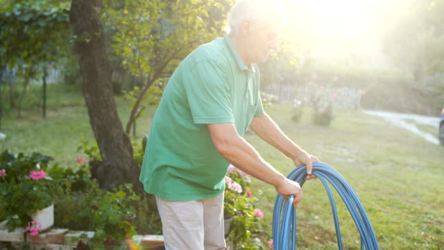 senior man is collecting a hose in the yard - pipe stock videos & royalty-free footage